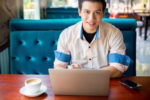 Młody człowiek pracuje z laptopem w kawiarni