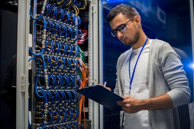 Młody człowiek pracuje z serwerami