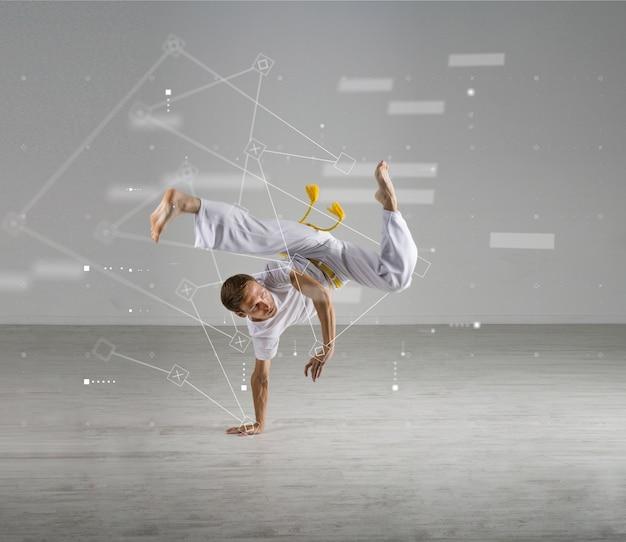 Młody człowiek praktykujący capoeira (brazylijska sztuka walki z elementami tańca, akrobatyki i muzyki. nauki o sporcie, biomechanika, koncepcja technologii informatycznych)