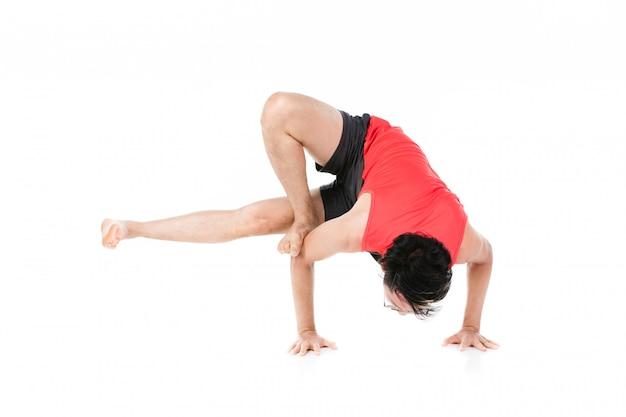 Młody człowiek praktykuje jogę na białym tle