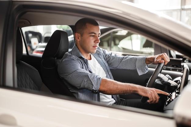Młody człowiek próbuje samochód w salonie