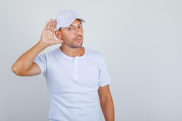 Młody człowiek próbuje usłyszeć gestem ucha w białej koszulce, widok z przodu czapki.