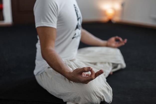 Młody człowiek profesjonalista siedzi w pozycji lotosu. trener robi jogi. zrelaksować się. zbliżenie