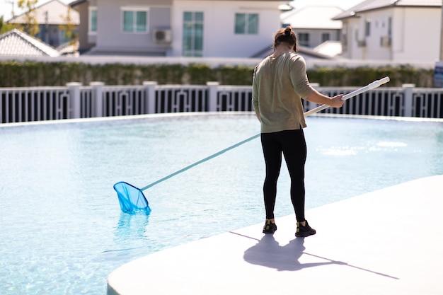 Młody człowiek profesjonalny pracownik sprzątający czyszczenie basenu z czerpakiem na zewnątrz.