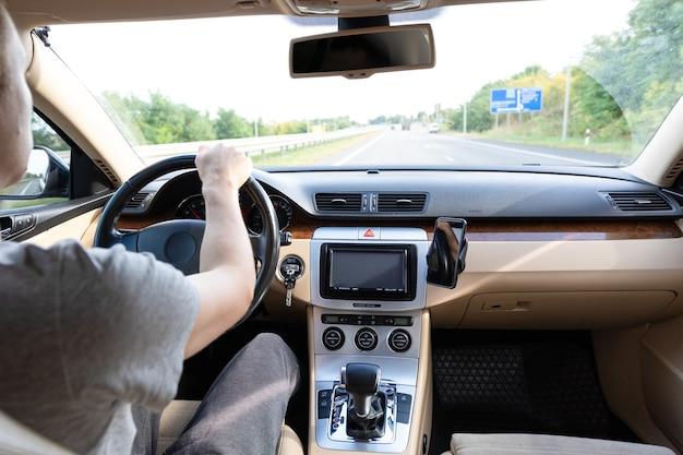 Młody człowiek prowadzący nowoczesny samochód na drodze asfaltowej