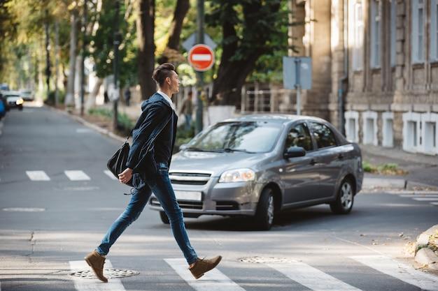 Młody człowiek przechodzi przez ulicę