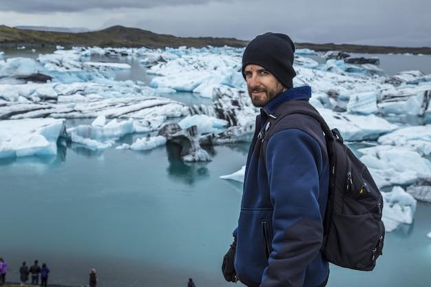 Młody człowiek przed małymi niebieskimi górami lodowymi w jeziorze lodowym jokulsarlon i bardzo szarym niebem na islandii