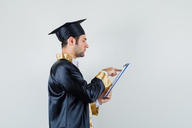 Młody Człowiek Przeglądając Notatki W Schowku W Mundurze Absolwenta I Patrząc Zajęty. Darmowe Zdjęcia