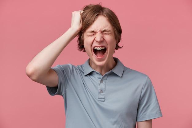 Młody człowiek przegrał w ważnych zawodach, złapał się za głowę, wyrywając sobie włosy na głowie, głośno krzyczy z szeroko otwartymi ustami, zamkniętymi oczami, na różowym tle. ludzie, negatywne reakcje i uczucia