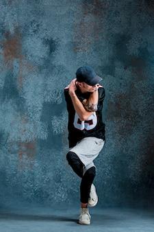 Młody człowiek przerwy taniec na ściennym tle.