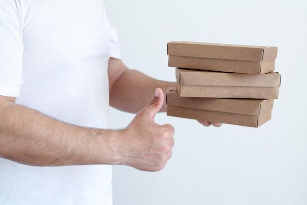 Młody człowiek przewożących rzemiosła eco pudełka do wysyłki. koncepcja dostawy paczki. kurier z paczkami w rękach w pomieszczeniu.