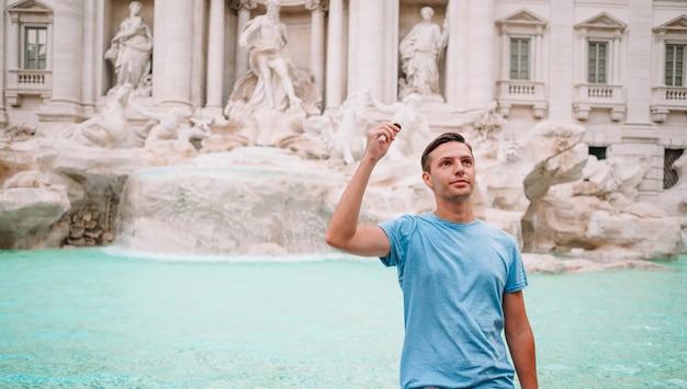 Młody człowiek przy fontannie fontana di trevi z monetami w rękach