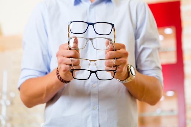 Młody człowiek przy optyka z szkłami
