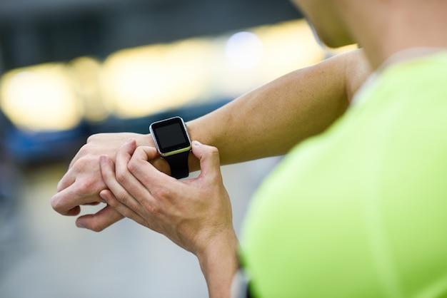 Młody człowiek przy użyciu smartwatch na siłowni