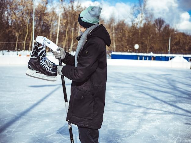 Młody człowiek przybywa do obręczy skate z kijem hokejowym i łyżwy
