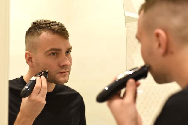 Młody człowiek przycinanie brody i patrząc w lustro w łazience