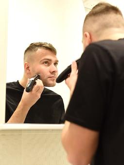 Młody człowiek przycinanie brody i patrząc w lustro