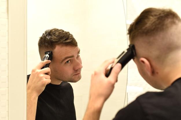Młody człowiek przycinanie włosów i patrząc w lustro