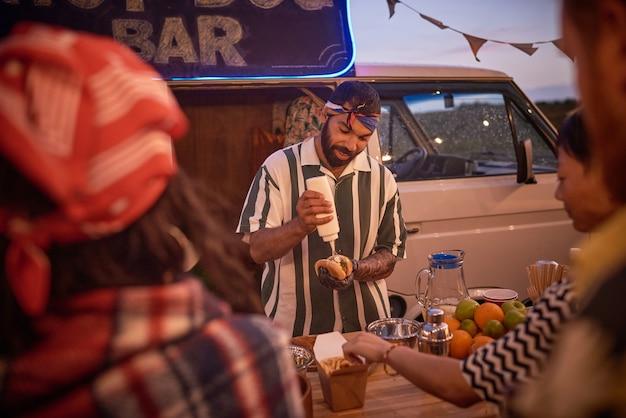 Młody człowiek przygotowuje hot doga dla ludzi na imprezie na plaży