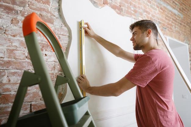 Młody człowiek przygotowuje się do naprawy mieszkania samodzielnie. przed remontem lub remontem domu. pojęcie relacji, rodziny, majsterkowania. pomiar ściany przed malowaniem lub wykonaniem projektu.