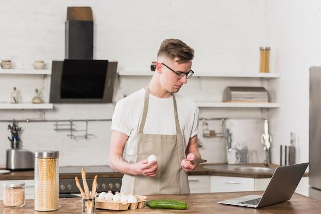 Młody człowiek przygotowywa jedzenie patrzeć jego laptop na stole