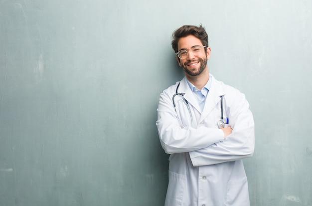 Młody człowiek przyjazny lekarz na ścianie grunge z kopia miejsce przekraczania jego broni