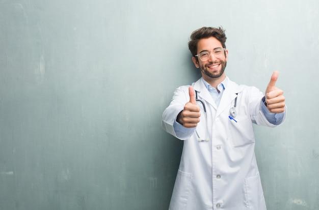 Młody człowiek przyjazny lekarz na ścianie grunge z kopią przestrzeni wesoły i podekscytowany