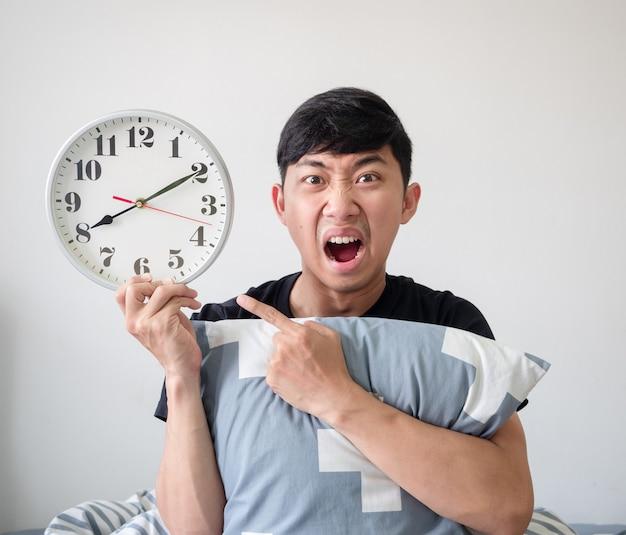 Młody człowiek przytula poduszkę i czuje się zszokowana twarz palcem wskazującym na zegar w jego ręce pracuje późno koncepcja