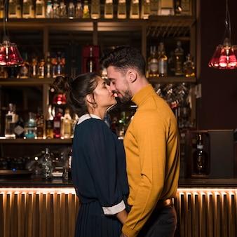 Młody człowiek przytulanie z uroczą kobietą w pobliżu kontuaru barowego