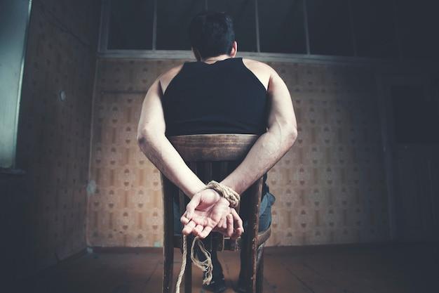 Młody człowiek przywiązany do krzesła