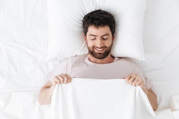 Młody człowiek rano pod kocem w łóżku leży patrząc na swoje genitalia