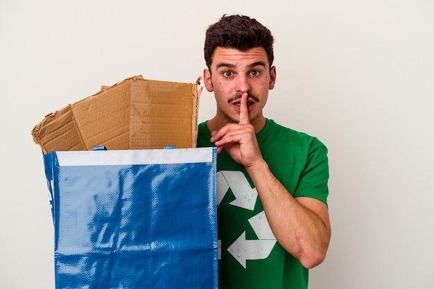 Młody człowiek rasy kaukaskiej recyklingu kartonu na białym tle