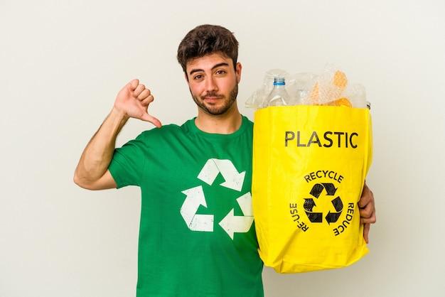 Młody człowiek rasy kaukaskiej recyklingu tworzyw sztucznych na białym tle czuje się dumny i pewny siebie, przykład do naśladowania.