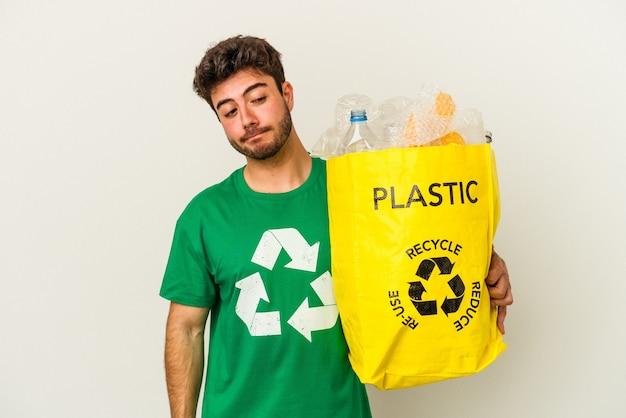 Młody człowiek rasy kaukaskiej recyklingu tworzyw sztucznych na białym tle mylić, czuje się wątpliwe i niepewne.