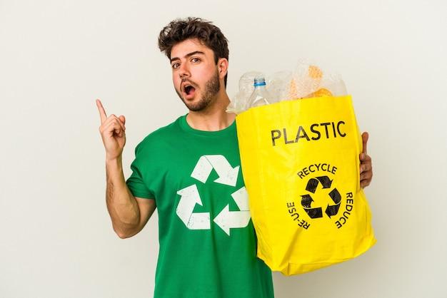 Młody człowiek rasy kaukaskiej recyklingu tworzyw sztucznych na białym tle, wskazując na bok