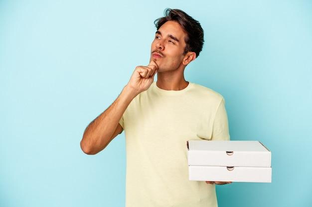 Młody człowiek rasy mieszanej gospodarstwa pizze na białym tle na niebieskim tle patrząc w bok z wyrazem wątpliwości i sceptyczny.