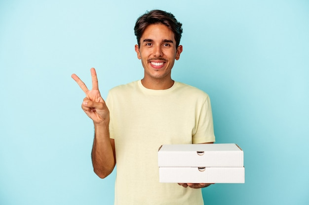 Młody człowiek rasy mieszanej gospodarstwa pizze na białym tle na niebieskim tle pokazano numer dwa palcami.