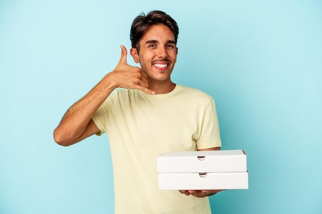 Młody człowiek rasy mieszanej gospodarstwa pizze na białym tle na niebieskim tle pokazując gest połączenia z telefonu komórkowego palcami.