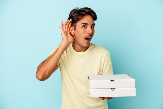 Młody człowiek rasy mieszanej gospodarstwa pizze na białym tle na niebieskim tle, próbując słuchać plotek.