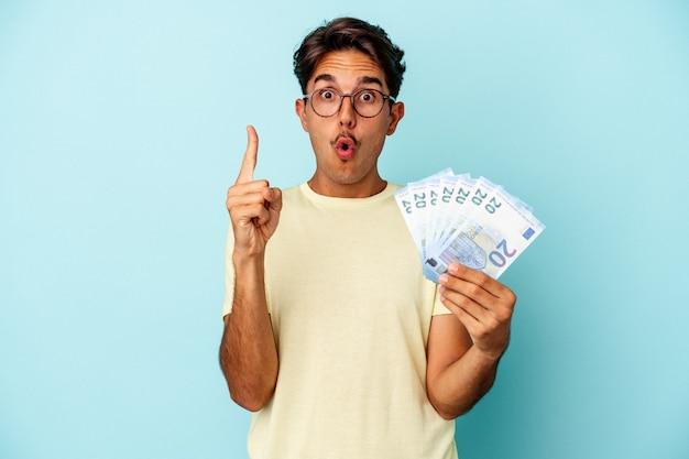 Młody człowiek rasy mieszanej gospodarstwa rachunki na białym tle na niebieskim tle o jakiś świetny pomysł, pojęcie kreatywności.
