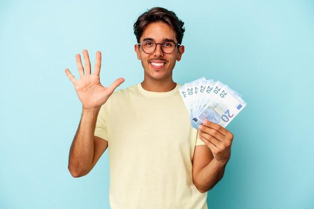 Młody człowiek rasy mieszanej gospodarstwa rachunki na białym tle na niebieskim tle uśmiechnięty wesoły pokazano numer pięć palcami.