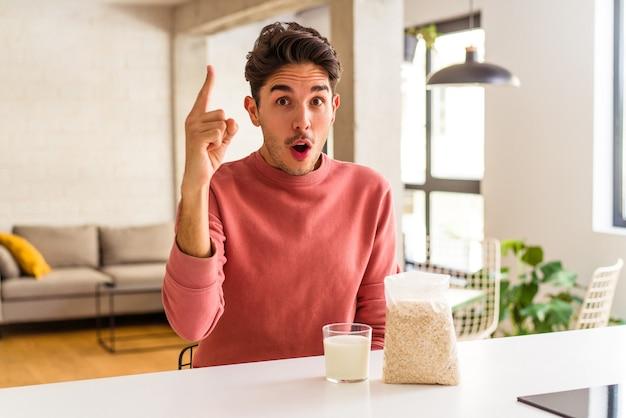 Młody człowiek rasy mieszanej jedzący płatki owsiane i mleko na śniadanie w swojej kuchni mający pomysł, koncepcję inspiracji.