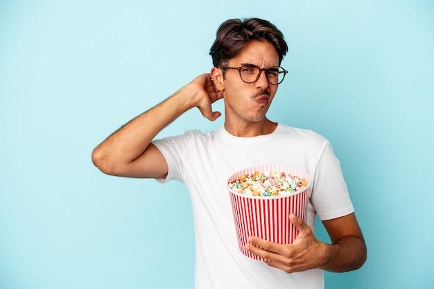 Młody człowiek rasy mieszanej jedzenie popcornów na białym tle na niebieskim tle dotykając tyłu głowy, myśląc i dokonując wyboru.