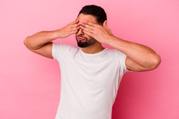 Młody człowiek rasy mieszanej na białym tle na różowy przestraszony obejmujących oczy rękami.