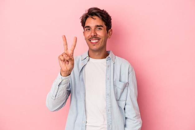 Młody człowiek rasy mieszanej na białym tle pokazano numer dwa palcami.