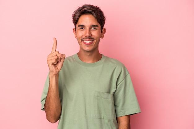 Młody człowiek rasy mieszanej na białym tle pokazano numer jeden z palcem.