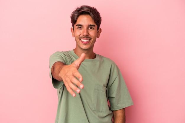Młody człowiek rasy mieszanej na białym tle rozciągania ręki na aparat w geście pozdrowienia.