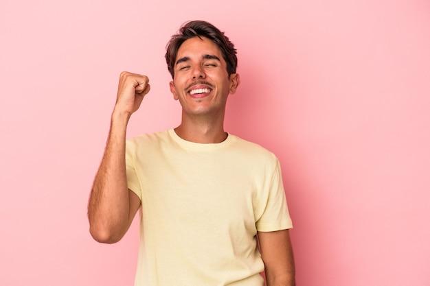 Młody człowiek rasy mieszanej na białym tle świętuje zwycięstwo, pasję i entuzjazm, szczęśliwy wyraz.