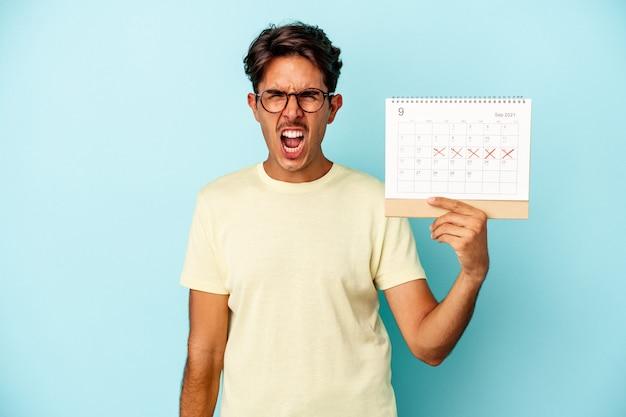 Młody człowiek rasy mieszanej posiadający kalendarz na białym tle na niebieskim tle krzyczy bardzo zły i agresywny.