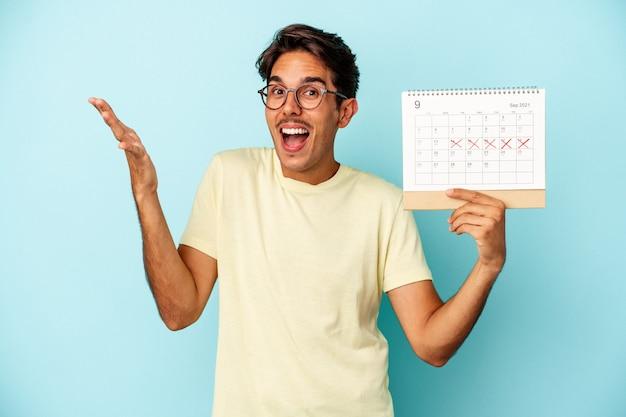 Młody człowiek rasy mieszanej posiadający kalendarz na białym tle na niebieskim tle otrzymujący miłą niespodziankę, podekscytowany i podnoszący ręce.